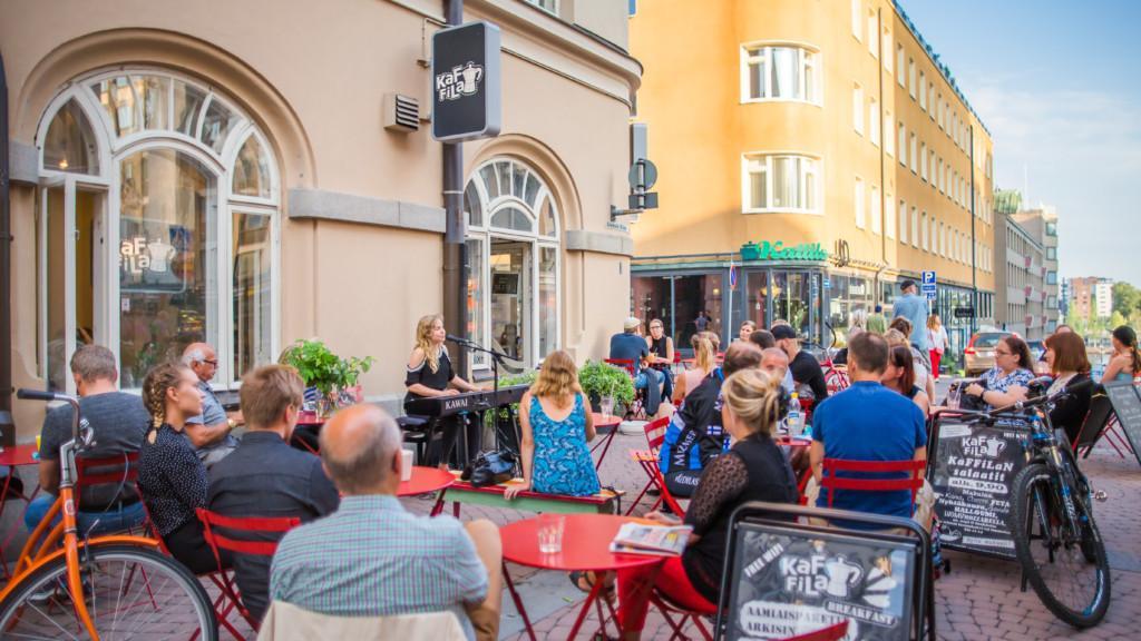 Ihmisiä Tampereen kesäterassilla kuuntelemassa musiikkia.