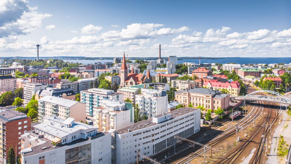 Näkymä Tampereen rakennuksista ja junaradasta ylhäältä dronella kuvattuna.